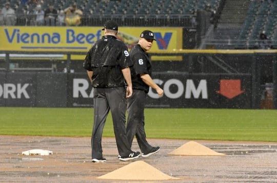 May 27, 2019; Chicago, IL, USA; Umpire's Chris Conroy (98) and Mark Carlson (6) look at the condition of the field during the fifth inning of a game between the Chicago White Sox and the Kansas City Royals at Guaranteed Rate Field. Mandatory Credit: David Banks-USA TODAY Sports