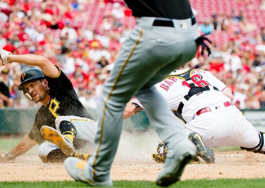 Pittsburgh Pirates second baseman Adam Frazier (26) scores as Cincinnati Reds catcher Tucker Barnhart (16) attempts to tag him out in the eighth inning of the MLB National League game between Cincinnati Reds and Pittsburgh Pirates at Great American Ball Park in Cincinnati on Monday, May 27, 2019.   Pittsburgh Pirates At Cincinnati Reds