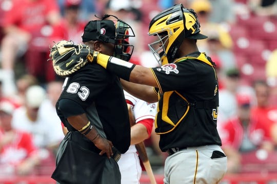May 27, 2019; Cincinnati, OH, USA; MLB umpire Laz Diaz (63) talks with Pittsburgh Pirates catcher Elias Diaz (32) during a stop in play against the Cincinnati Reds in the eighth inning at Great American Ball Park. Mandatory Credit: Aaron Doster-USA TODAY Sports