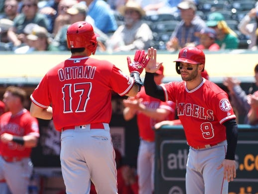 May 29, 2019; Oakland, CA, USA; Los Angeles Angels designated hitter Shohei Ohtani (17) high fives third baseman Tommy La Stella (9) after scoring against the Oakland Athletics during the first inning at Oakland Coliseum. Mandatory Credit: Kelley L Cox-USA TODAY Sports