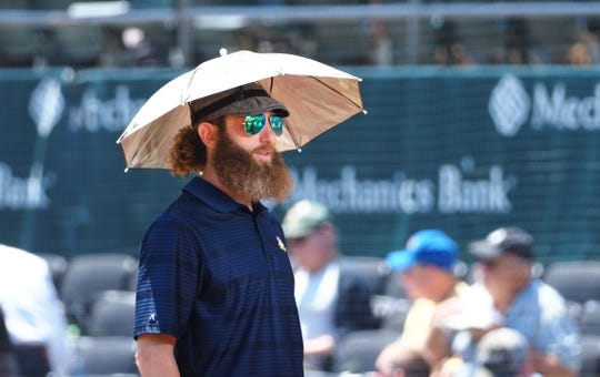 May 29, 2019; Oakland, CA, USA; Oakland Athletics broadcaster and former pitcher, Dallas Braden, wears an umbrella hat before the game against the Los Angeles Angels at Oakland Coliseum. Mandatory Credit: Kelley L Cox-USA TODAY Sports
