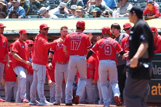 May 29, 2019; Oakland, CA, USA; Los Angeles Angels designated hitter Shohei Ohtani (17) and third baseman Tommy La Stella (9) celebrate with teammates after scoring runs against the Oakland Athletics during the first inning at Oakland Coliseum. Mandatory Credit: Kelley L Cox-USA TODAY Sports