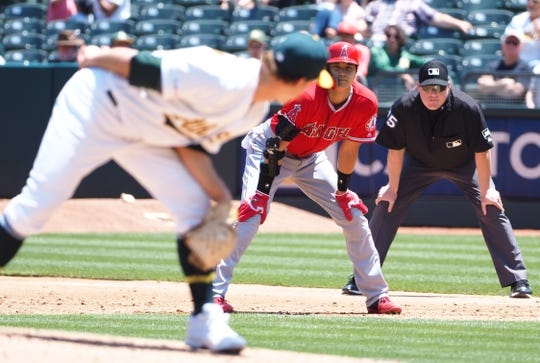 May 29, 2019; Oakland, CA, USA; Oakland Athletics relief pitcher Daniel Mengden (33) looks over his shoulder as Los Angeles Angels designated hitter Shohei Ohtani (17) takes a lead off first base during the third inning at Oakland Coliseum. Mandatory Credit: Kelley L Cox-USA TODAY Sports