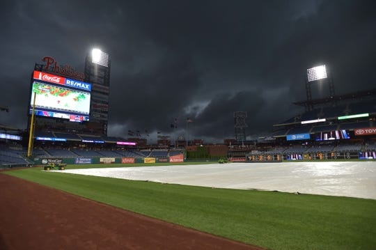 May 29, 2019; Philadelphia, PA, USA; Grounds crew covers the field in a rain delay before the game between the Philadelphia Phillies and the St. Louis Cardinals at Citizens Bank Park. Mandatory Credit: John Geliebter-USA TODAY Sports
