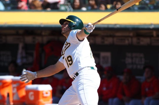 May 29, 2019; Oakland, CA, USA; Oakland Athletics catcher Josh Phegley (19) hits a sacrifice fly to send in a run against the Los Angeles Angels during the ninth inning at Oakland Coliseum. Mandatory Credit: Kelley L Cox-USA TODAY Sports