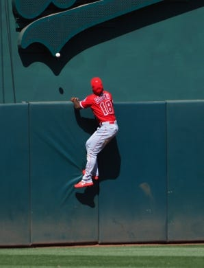 May 29, 2019; Oakland, CA, USA; Los Angeles Angels center fielder Brian Goodwin (18) jumps along the fence on an Oakland Athletics home run during the ninth inning at Oakland Coliseum. Mandatory Credit: Kelley L Cox-USA TODAY Sports