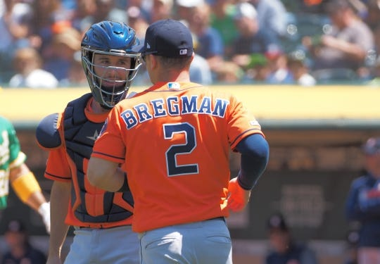 Jun 2, 2019; Oakland, CA, USA; Houston Astros third baseman Alex Bregman (2) reacts with catcher Garrett Stubbs (11) after catching a foul ball for an out against the Oakland Athletics during the fourth inning at Oakland Coliseum. Mandatory Credit: Kelley L Cox-USA TODAY Sports