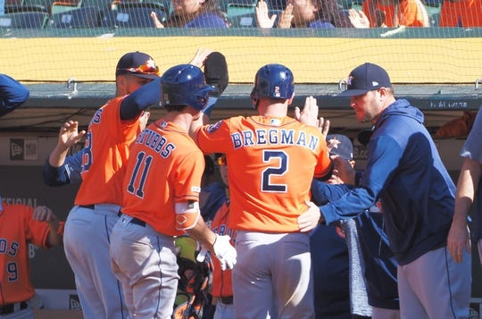 Jun 2, 2019; Oakland, CA, USA; Houston Astros third baseman Alex Bregman (2) high fives teammates in the dugout after scoring a run against the Oakland Athletics during the twelfth inning at Oakland Coliseum. Mandatory Credit: Kelley L Cox-USA TODAY Sports