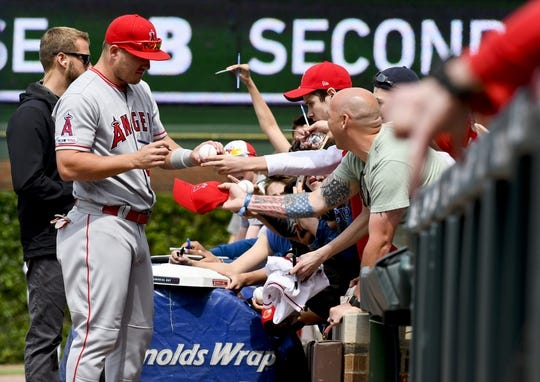 Jun 3, 2019; Chicago, IL, USA; Los Angeles Angels center fielder Mike Trout (27) signs autographs before the game against the Chicago Cubs at Wrigley Field. Mandatory Credit: Matt Marton-USA TODAY Sports