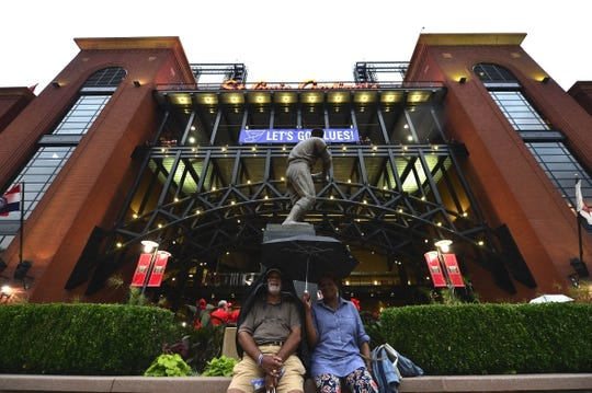 Jun 4, 2019; St. Louis, MO, USA; Fans wait out a rain delay in front of the Stan Musial Statue prior to a game between the St. Louis Cardinals and the Cincinnati Reds at Busch Stadium. Mandatory Credit: Jeff Curry-USA TODAY Sports