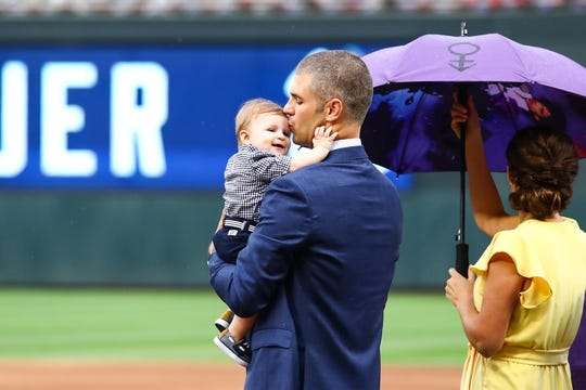 Jun 15, 2019; Minneapolis, MN, USA; Minnesota Twins former player Joe Mauer  kisses his son during Mauer's number retirement ceremony before the start of a game against the Kansas City Royals at Target Field. Mandatory Credit: David Berding-USA TODAY Sports