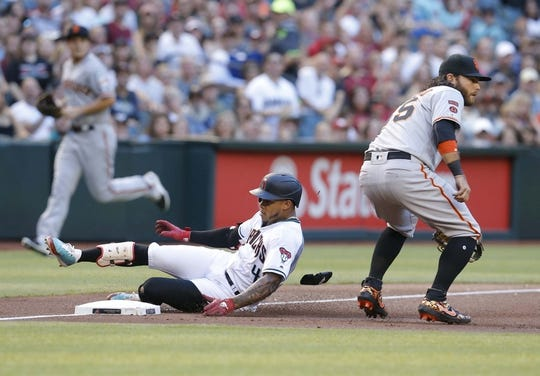 Jun 21, 2019; Phoenix, AZ, USA; Arizona Diamondbacks center fielder Ketel Marte (4) slides into thirdbase after hitting a triple in front of San Francisco Giants shortstop Brandon Crawford (35) in the first inning during a baseball game at Chase Field. Mandatory Credit: Rick Scuteri-USA TODAY Sports