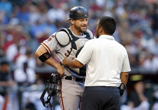 Jun 21, 2019; Phoenix, AZ, USA; San Francisco Giants catcher Stephen Vogt (21) talks with his Trainer after getting hit with a bat from Arizona Diamondbacks center fielder Adam Jones (10) in the first inning during a baseball game at Chase Field. Mandatory Credit: Rick Scuteri-USA TODAY Sports