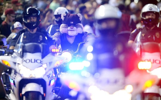 Jun 23, 2019; Phoenix, AZ, USA; Arizona Diamondbacks mascot Baxter The Bobcat rides a motorcycle along police officers prior to the first inning against the San Francisco Giants at Chase Field. Mandatory Credit: Joe Camporeale-USA TODAY Sports