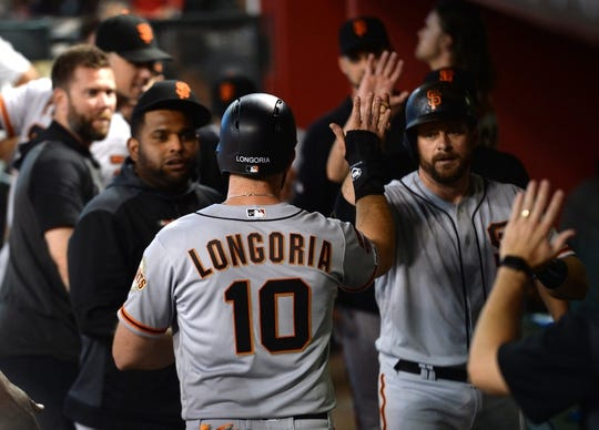 Jun 23, 2019; Phoenix, AZ, USA; San Francisco Giants third baseman Evan Longoria (10) and San Francisco Giants catcher Stephen Vogt (21) slap hands after Vogt drove in Longoria during the fourth inning at Chase Field. Mandatory Credit: Joe Camporeale-USA TODAY Sports