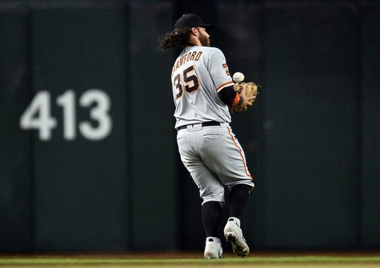Jun 23, 2019; Phoenix, AZ, USA; San Francisco Giants shortstop Brandon Crawford (35) misplays a pop up against the Arizona Diamondbacks during the seventh inning at Chase Field. Mandatory Credit: Joe Camporeale-USA TODAY Sports