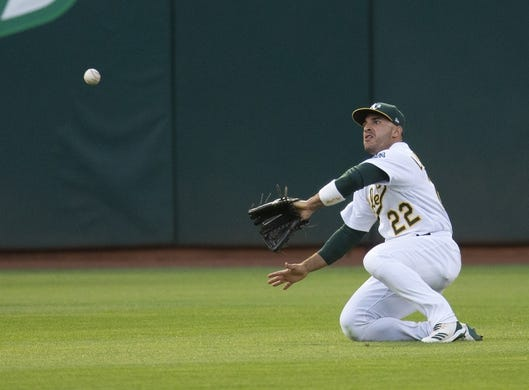 Jul 3, 2019; Oakland, CA, USA; Oakland Athletics center fielder Ramon Laureano (22) makes a sliding catch of a line drive by Minnesota Twins designated hitter Jorge Polanco during the sixth inning of a baseball game at Oakland Coliseum. Mandatory Credit: D. Ross Cameron-USA TODAY Sports