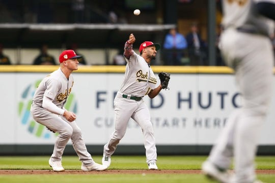 Jul 5, 2019; Seattle, WA, USA; Oakland Athletics shortstop Marcus Semien (10) throws to first for an out against the Seattle Mariners during the first inning at T-Mobile Park. Oakland Athletics third baseman Matt Chapman (26) reacts at left. Mandatory Credit: Joe Nicholson-USA TODAY Sports