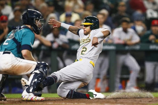 Jul 5, 2019; Seattle, WA, USA; Oakland Athletics designated hitter Khris Davis (2) slides home to score a run against the Seattle Mariners during the seventh inning at T-Mobile Park. Mandatory Credit: Joe Nicholson-USA TODAY Sports
