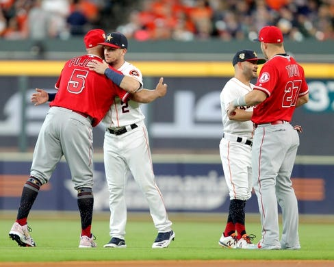 Jul 5, 2019; Houston, TX, USA; Los Angeles Angels first baseman Albert Pujols (5) and Los Angeles Angels center fielder Mike Trout (27) both greet Houston Astros third baseman Alex Bregman (2) and Houston Astros second baseman Jose Altuve (27) prior to the game at Minute Maid Park. Mandatory Credit: Erik Williams-USA TODAY Sports