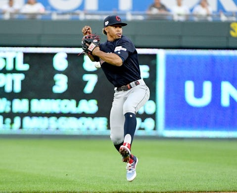 Jul 25, 2019; Kansas City, MO, USA; Cleveland Indians shortstop Francisco Lindor (12) loses the ball as he attempts to throw to first base against the Kansas City Royals in the third inning at Kauffman Stadium. Mandatory Credit: Denny Medley-USA TODAY Sports
