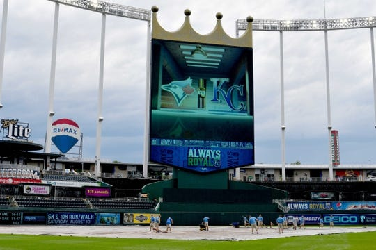 Jul 31, 2019; Kansas City, MO, USA; Members of the Kansas City Royals grounds crew clean off the tarp on the field before putting it away prior to the game against the Toronto Blue Jays at Kauffman Stadium. Mandatory Credit: Denny Medley-USA TODAY Sports