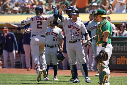 Aug 18, 2019; Oakland, CA, USA; Houston Astros third baseman Alex Bregman (2) is congratulated by right fielder Josh Reddick (22) after hitting a home run during the fifth inning against the Oakland Athletics at Oakland Coliseum. Mandatory Credit: Darren Yamashita-USA TODAY Sports