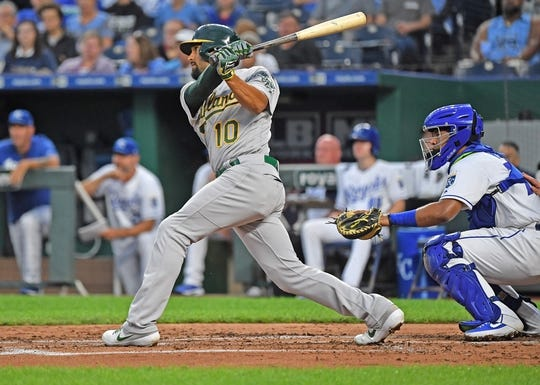 Aug 26, 2019; Kansas City, MO, USA; Oakland Athletics shortstop Marcus Semien (10) triples in three runs during the second inning against the Kansas City Royals at Kauffman Stadium. Mandatory Credit: Peter G. Aiken