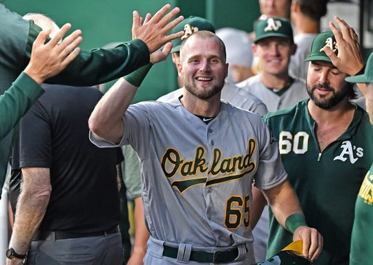 Aug 26, 2019; Kansas City, MO, USA; Oakland Athletics left fielder Seth Brown (65) celebrates in the dugout after scoring a run during the second inning against the Kansas City Royals at Kauffman Stadium. Mandatory Credit: Peter G. Aiken