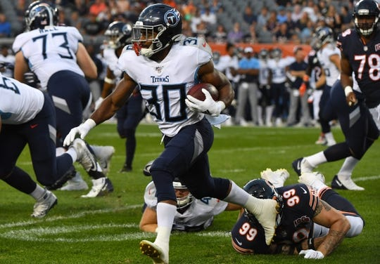 Aug 29, 2019; Chicago, IL, USA; Tennessee Titans running back Jeremy McNichols (30) rushes the ball past Chicago Bears outside linebacker Aaron Lynch (99) during the first half at Soldier Field. Mandatory Credit: Mike DiNovo-USA TODAY Sports