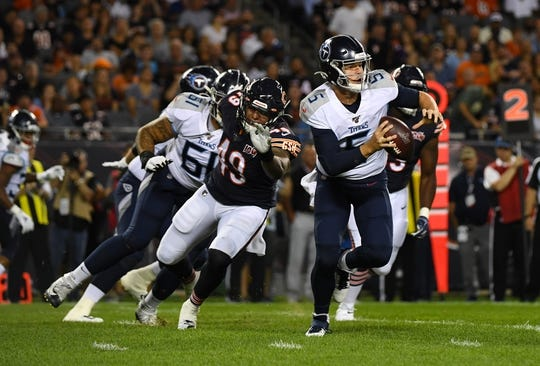 Aug 29, 2019; Chicago, IL, USA; Tennessee Titans quarterback Logan Woodside (5) rushes the ball past Chicago Bears tight end Ian Bunting (49) during the first half at Soldier Field. Mandatory Credit: Mike DiNovo-USA TODAY Sports