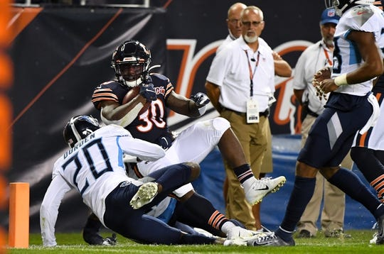 Aug 29, 2019; Chicago, IL, USA; Chicago Bears running back Josh Caldwell (30) rushes the ball against Tennessee Titans defensive back Kenneth Durden (20) during the first half at Soldier Field. Mandatory Credit: Mike DiNovo-USA TODAY Sports