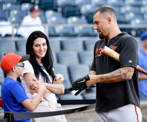 Aug 30, 2019; Kansas City, MO, USA; Baltimore Orioles second baseman Jace Peterson (23) signs an autograph for a young fan during batting practice before the game against the Kansas City Royals at Kauffman Stadium. Mandatory Credit: Denny Medley-USA TODAY Sports