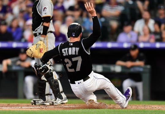Aug 31, 2019; Denver, CO, USA; Colorado Rockies shortstop Trevor Story (27) slides home to score a run in the third inning against the Pittsburgh Pirates at Coors Field. Mandatory Credit: Ron Chenoy-USA TODAY Sports