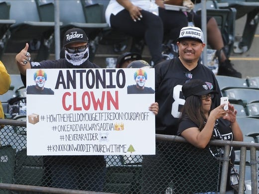 Sep 9, 2019; Oakland, CA, USA; An Oakland Raiders fan holds a sign reading  Antonio clown  referring to the release of receiver Antonio Brown (not pictured) before the game against the Denver Broncos at Oakland Coliseum. Mandatory Credit: Kelley L Cox-USA TODAY Sports