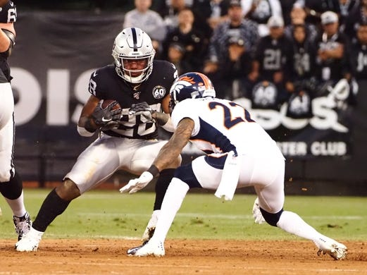 Sep 9, 2019; Oakland, CA, USA; Oakland Raiders running back Josh Jacobs (28) carries the ball against Denver Broncos defensive back Kareem Jackson (22) during the first quarter at Oakland Coliseum. Mandatory Credit: Kelley L Cox-USA TODAY Sports
