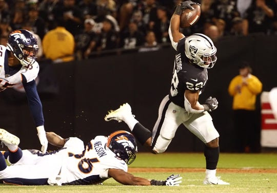Sep 9, 2019; Oakland, CA, USA; Oakland Raiders running back Josh Jacobs (28) escapes Denver Broncos linebacker Corey Nelson (56) during the first quarter at Oakland Coliseum. Mandatory Credit: Kelley L Cox-USA TODAY Sports