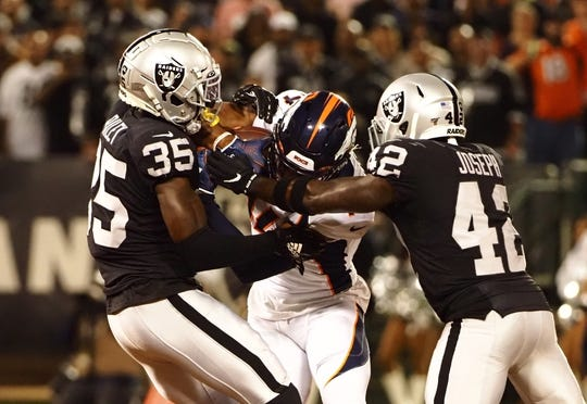 Sep 9, 2019; Oakland, CA, USA; Oakland Raiders free safety Curtis Riley (35) and free safety Karl Joseph (42) combine against Denver Broncos wide receiver Courtland Sutton (14) during the first quarter at Oakland Coliseum. Mandatory Credit: Kelley L Cox-USA TODAY Sports