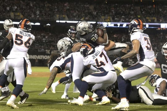 Sep 9, 2019; Oakland, CA, USA; Oakland Raiders running back Josh Jacobs (28) scores on a 2-yard touchdown run in the second quarter against the Denver Broncos at Oakland-Alameda County Coliseum. Mandatory Credit: Kirby Lee-USA TODAY Sports