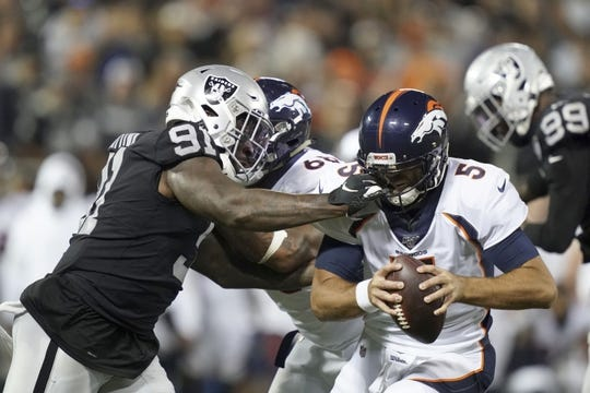 Sep 9, 2019; Oakland, CA, USA; Denver Broncos quarterback Joe Flacco (5) is tackled by Oakland Raiders defensive end Benson Mayowa (91) in the second half at Oakland-Alameda County Coliseum. The Raiders defeated The Broncos 24-16.  Mandatory Credit: Kirby Lee-USA TODAY Sports
