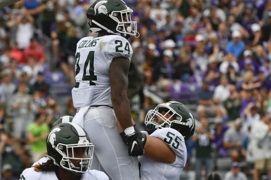 Sep 21, 2019; Evanston, IL, USA; Michigan State Spartans offensive tackle Jordan Reid (55) lifts up Michigan State Spartans running back Elijah Collins (24) after he scored a touchdown against the Northwestern Wildcats during the first half at Ryan Field. Mandatory Credit: Matt Marton-USA TODAY Sports