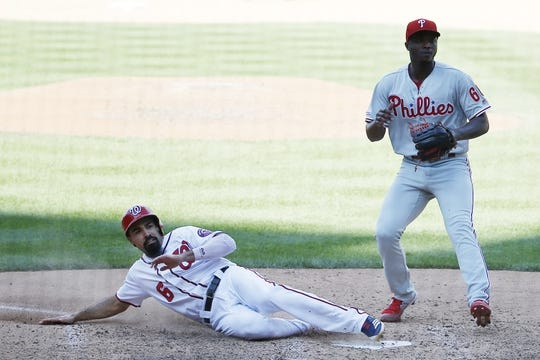 Sep 24, 2019; Washington, DC, USA; Washington Nationals third baseman Anthony Rendon (6) slides across home plate to score a run on a wild pitch by Philadelphia Phillies relief pitcher Edgar Garcia (66) in the eighth inning at Nationals Park. Mandatory Credit: Geoff Burke-USA TODAY Sports