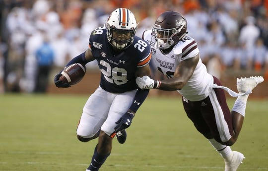 Sep 28, 2019; Auburn, AL, USA;  Auburn Tigers running back JaTarvious Whitlow (28) is tackled by Mississippi State Bulldogs linebacker Leo Lewis (10) during the first quarter at Jordan-Hare Stadium. Mandatory Credit: John Reed-USA TODAY Sports