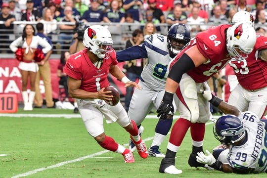 Sep 29, 2019; Glendale, AZ, USA; Arizona Cardinals quarterback Kyler Murray (1) escapes a tackle by Seattle Seahawks defensive tackle Poona Ford (97) in the first half  at State Farm Stadium. Mandatory Credit: Matt Kartozian-USA TODAY Sports