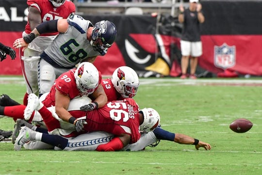 Sep 29, 2019; Glendale, AZ, USA; Seattle Seahawks quarterback Russell Wilson (3) fumbles while being sacked by Arizona Cardinals outside linebacker Terrell Suggs (56) and middle linebacker Jordan Hicks (58) during the second half at State Farm Stadium. Mandatory Credit: Matt Kartozian-USA TODAY Sports