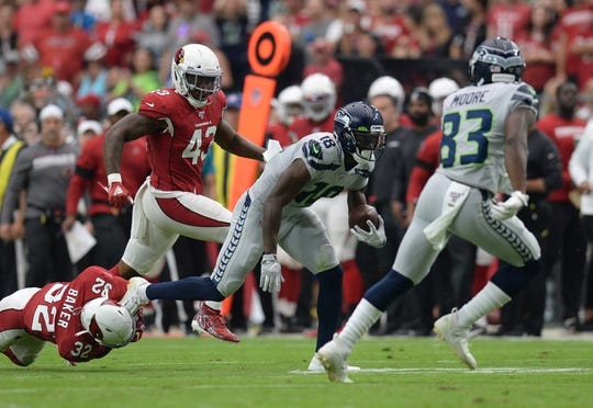 Sep 29, 2019; Glendale, AZ, USA; Seattle Seahawks wide receiver Jaron Brown (18) breaks the tackle of Arizona Cardinals strong safety Budda Baker (32) during the first half at State Farm Stadium. Mandatory Credit: Joe Camporeale-USA TODAY Sports