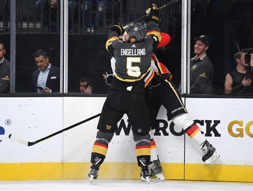 Oct 12, 2019; Las Vegas, NV, USA; Vegas Golden Knights defenseman Deryk Engelland (5) checks Calgary Flames left wing Milan Lucic (17) during the first period at T-Mobile Arena. Mandatory Credit: Stephen R. Sylvanie-USA TODAY Sports