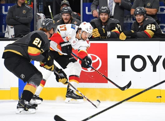 Oct 12, 2019; Las Vegas, NV, USA; Calgary Flames right wing Michael Frolik (67) shoots during the first period against the Vegas Golden Knights at T-Mobile Arena. Mandatory Credit: Stephen R. Sylvanie-USA TODAY Sports