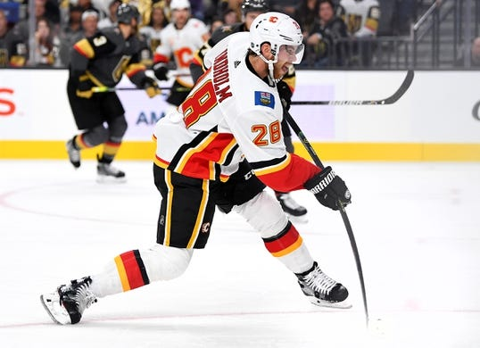 Oct 12, 2019; Las Vegas, NV, USA; Calgary Flames center Elias Lindholm (28) shoots during the first period against the Vegas Golden Knights at T-Mobile Arena. Mandatory Credit: Stephen R. Sylvanie-USA TODAY Sports