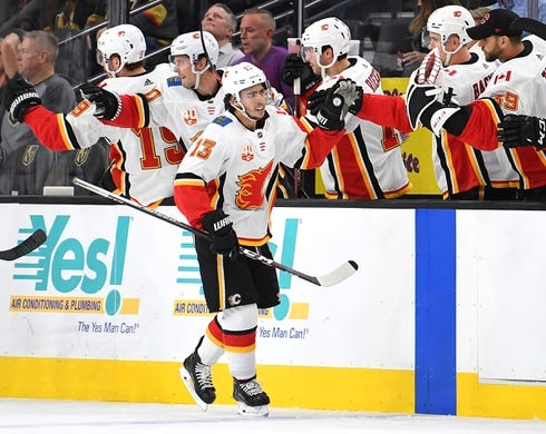 Oct 12, 2019; Las Vegas, NV, USA; Calgary Flames left wing Johnny Gaudreau (13) celebrates with team mates after scoring a second period goal against the Vegas Golden Knights at T-Mobile Arena. Mandatory Credit: Stephen R. Sylvanie-USA TODAY Sports